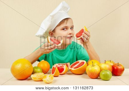 Funny kid in chefs hat with two slices of grapefruit at the table with fruits