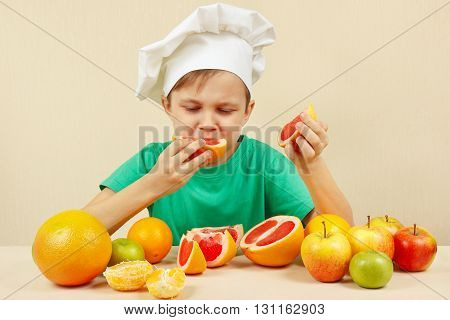 Little funny boy eat acidic grapefruit at the table with fruits
