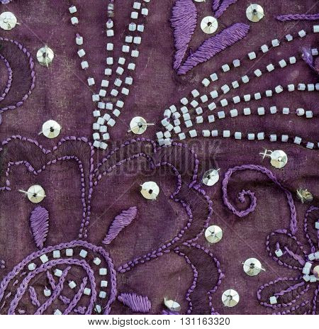 Close up detail of vintage sari fabric with embellishments. Purple background.