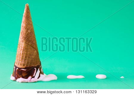 Strawberry ice cream cone on green background