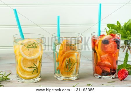 Side view of detox water cocktails on wooden table.
