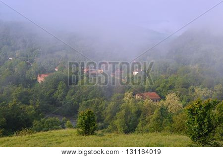 VETRINTSI VILLAGE, VELIKO TARNOVO PROVINCE, BULGARIA - MAY 8, 2016: Foggy morning in the mountain village in the Balkans