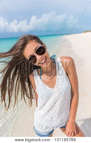 Happy aviator sunglasses woman beach fun playful with healthy hair. Beautiful young Asian model posing smiling at camera enjoying summer holidays on tropical destination on Caribbean travel.