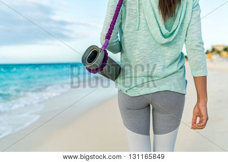 Fitness woman carrying yoga mat with strap on beach going to class training. Closeup of sports equipment, back view of fit athlete in activewear showing fashion leggings and turquoise hoodie.