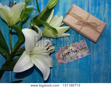 white Lily flower lying on blue wooden boards, next to the piece of paper where it is written