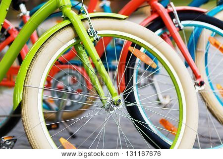 Three beautiful lady city bright colored bicycles or bikes for woman standing in the summer park outdoors, wheel closeup