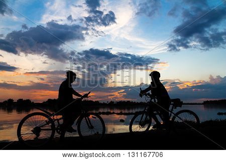 silhouette bike girl at sunset beside the river in countryside of Thailand