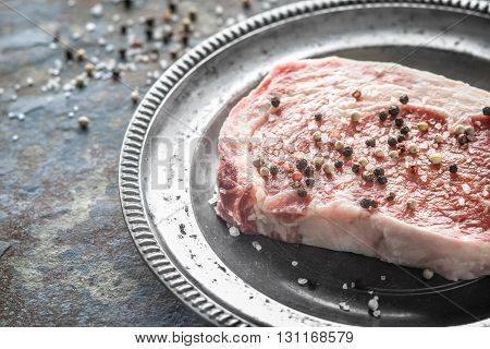 Piece of ribeye steak and peppercorn and salt on a plate of tin horizontal