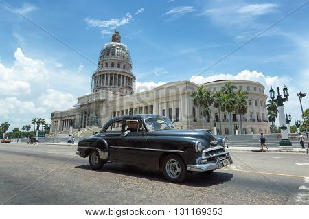 Havana, Cuba - June 22, 2015: A black american vintage  car passing in front of the Capitolio in Old Havana