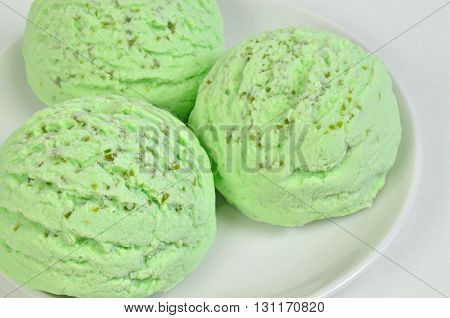 three  scoops of green ice cream, pistachio, woodruff, peppermint or kiwi flavor,  on white plate, close up, horizontal, full frame