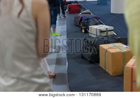 Line of luggage and belonging and people waiting for claims on arrival flight at the airport's carousel