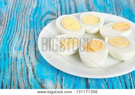 Boiled hen eggs in a white plate on a blue wooden background