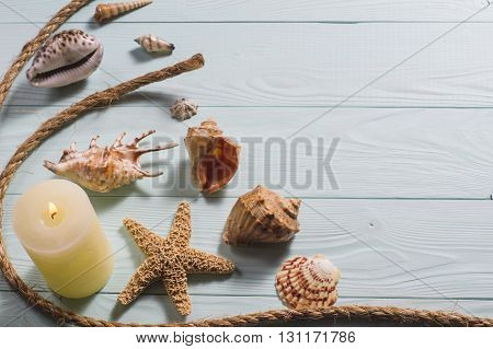 Concept of the summer time with fish star and sea shells on the wooden blue background, flat lay. Summer time sea vacation.