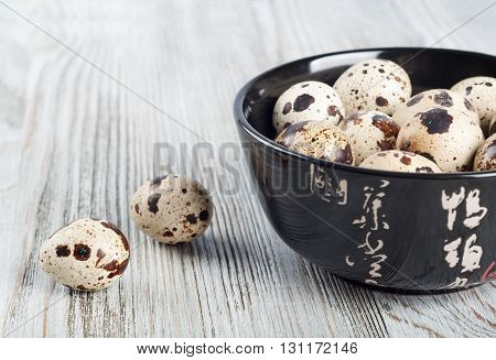 Quail eggs in a black dish on a wooden background.