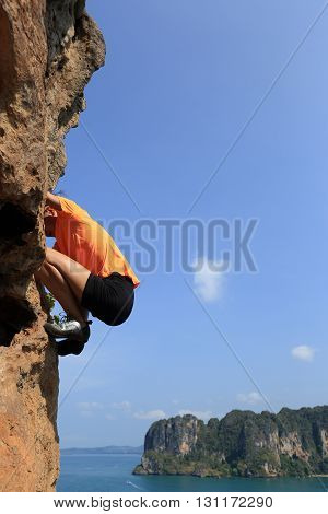 young woman rock climber climbing on seasie rock