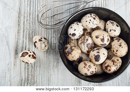 Quail eggs in a black dish on a wooden background. Top view.