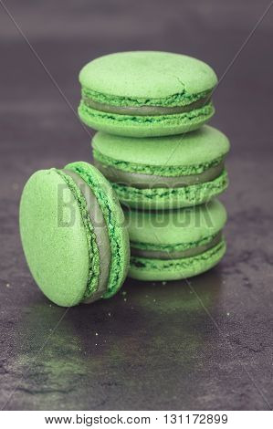 Green macaron. A stack of green tea  macaron on rustic background.   Macro, selective focus, vintage toned image