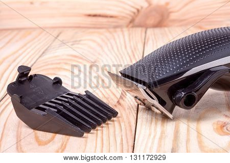 hair trimmer  with attachment on a light wooden background closeup.