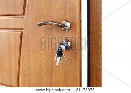 Open door handle. Door lock with keys. Brown wooden door closeup isolated. Modern interior design, door handle. New house concept. Real estate.