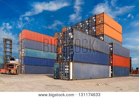Colorful containers stacked at harbor freight terminal against blue sky background