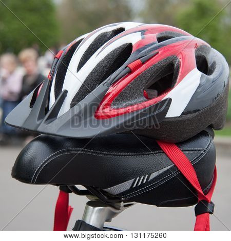 Cycling helmet on a bicycle seat closeup in summer park