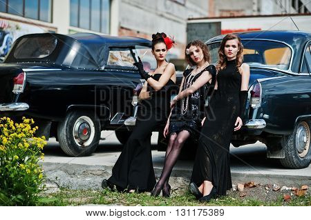Three Young Girl In Retro Style Dress Near Old Classic Vintage Cars.