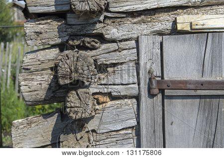 Corner of old wooden barn. The logs closeup. Part of door