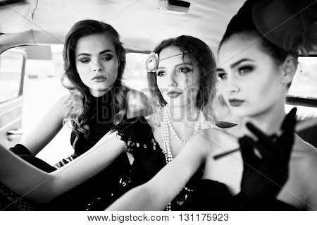 Three Young Girl In Retro Style Dress Seat On Old Classic Vintage Car.