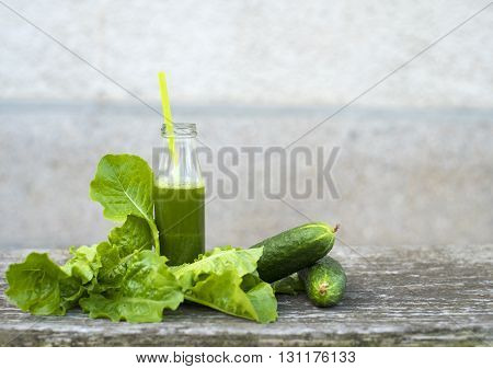 Spinach smoothie. Healthy green smoothie with spinach and cucumber in a jar mug on old wood