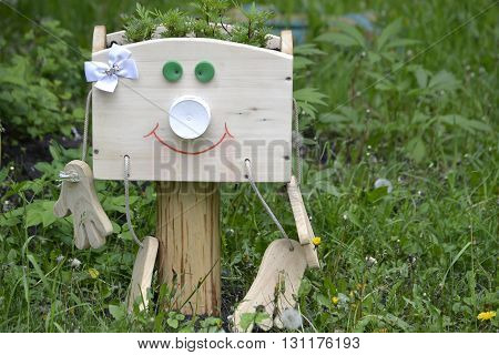 landscaping design flower bed a wooden box - smiling little face with her hands with a green plant