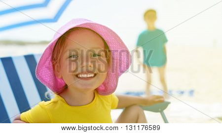 child close up portrait happy smile summer camp sitting chair umbrella selective focus backlight