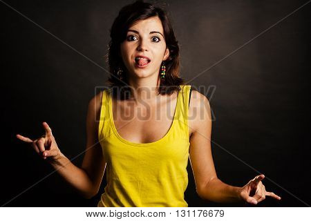 Silly young woman showing rock on sign - isolated on black.