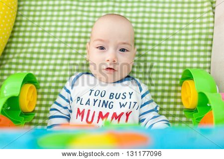 Portrait of an adorable child lying in bed looking at photographer.