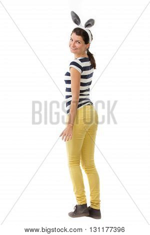 Young funny woman wearing rabbit ears is looking backwards - isolated on white