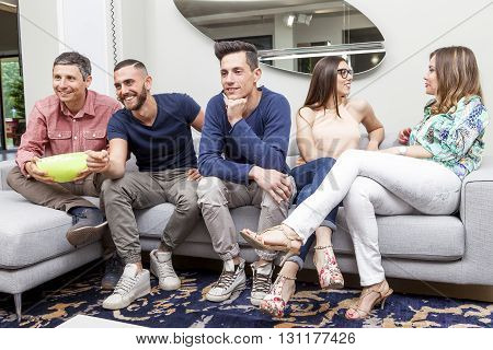 Group Of Friends Watching Tv And Eating Popcorn On Sofa