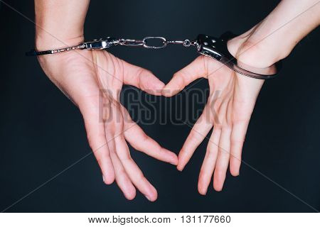 Handcuffed man's hands making a heart with fingers