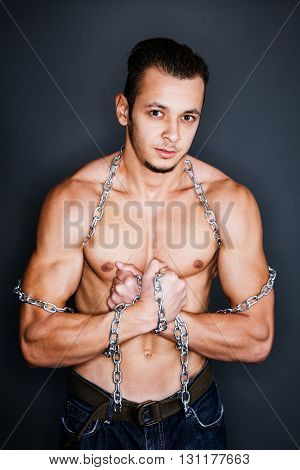 Muscular man being captive in steel chains
