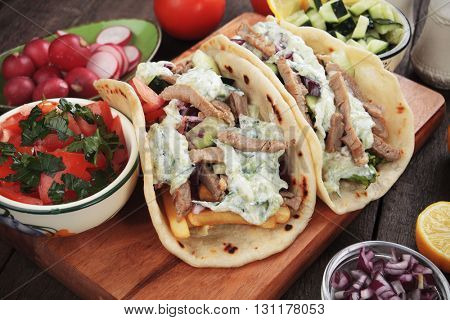 Gyros, greek pita bread wrapped sandwich with meat slices, tzatziki and fresh vegetables