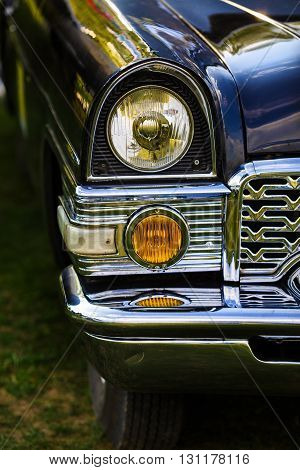Close-up of the headlights and the front part of an old black retro car. Classic vintage retro car. Selective focus on the car's headlight.