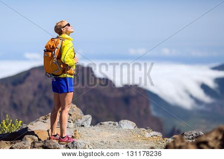 Woman successful hiking climbing in mountains motivation and inspiration landscape on island and ocean. Female hiker with backpack looking at beautiful view on La Palma Spain.
