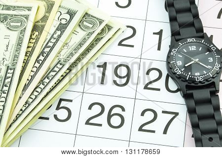 Close-up of time and money with calendar.