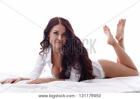 Beautiful brunette looking at camera while lying in bed