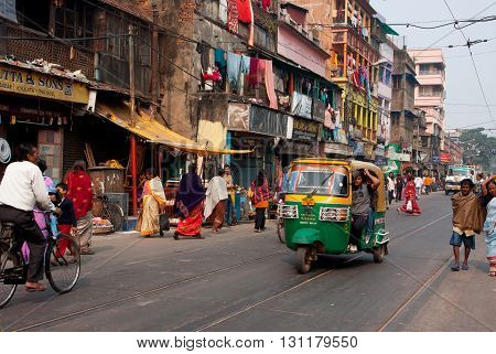KOLKATA, INDIA - JAN 11, 2013: Private auto rickshaw three-weeler tuk-tuk taxi drives down the street on January 11, 2013 in Kolkata. Indian three-wheelers have the design of the Piaggio Ape C from 1948