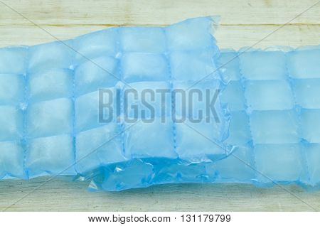Home ice made in cube bags on wooden background