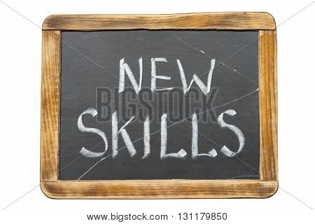 new skills phrase handwritten on vintage school slate board isolated on white