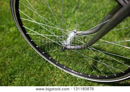 Classic road bicycle close-up photo in the summer green grass meadow field. Travel background.