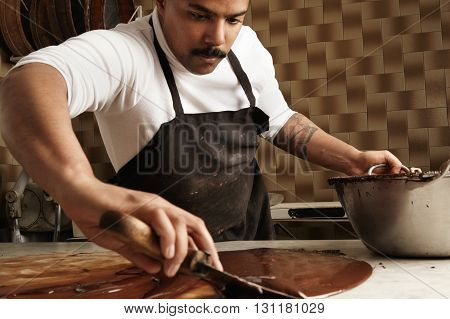 Close Up Professional Black Baker Collects Melted Cooled Chocolate From Marble Table To Steel Pot. A