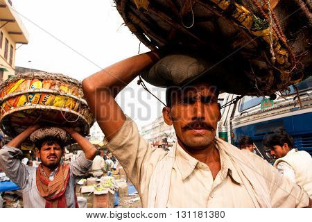 KOLKATA, INDIA - JANUARY 14, 2013: Food market workers suffer huge baskets on their heads on January 14, 2013 in Kolkata. Only 0.81 perc. of the Kolkata's workforce employed in the primary sector - agriculture