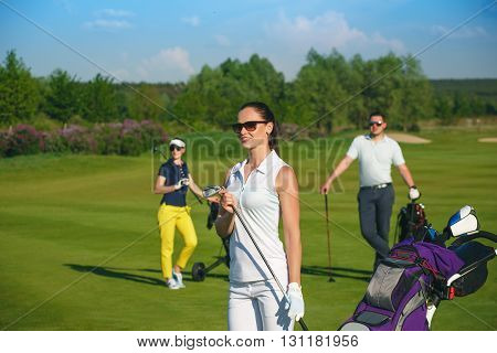 Portrait of young sportive women golfer playing golf with friends at sunny day
