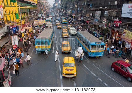 KOLKATA, INDIA - JAN 13, 2013: Antique yellow Ambassador taxi cabs down the busy street on January 13, 2013 in West Bengal. First Ambassador was produced by the Yellow Cab Manufacturing Company in 1921